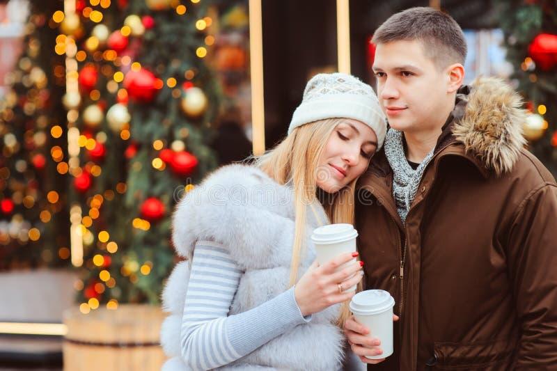 portrait de Noël des ajouter heureux au vin chaud ou au thé chaud marchant sur des rues de ville décorées pendant des vacances image libre de droits