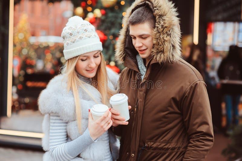 portrait de Noël des ajouter heureux au vin chaud ou au thé chaud marchant sur des rues de ville décorées pendant des vacances photographie stock