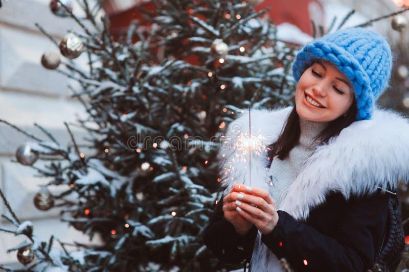 Portrait de Noël de jeune femme heureuse marchant dans la ville neigeuse d'hiver photos libres de droits