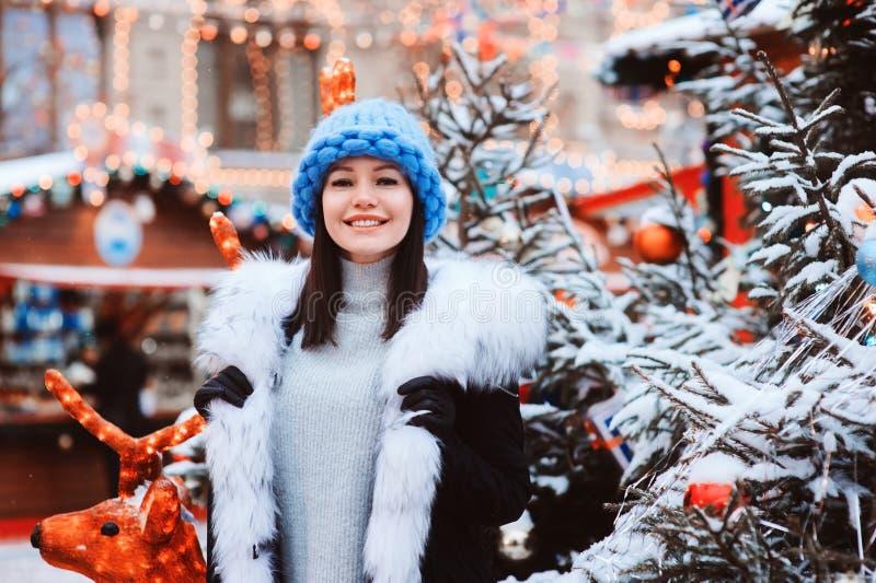 Portrait de Noël de jeune femme heureuse marchant dans la ville neigeuse d'hiver images libres de droits