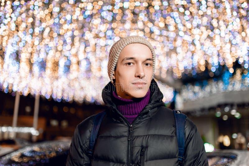 Portrait de nuit de ville d'un type beau et jeune chaudement habillé sur un fond des lumières dans le bokeh image stock