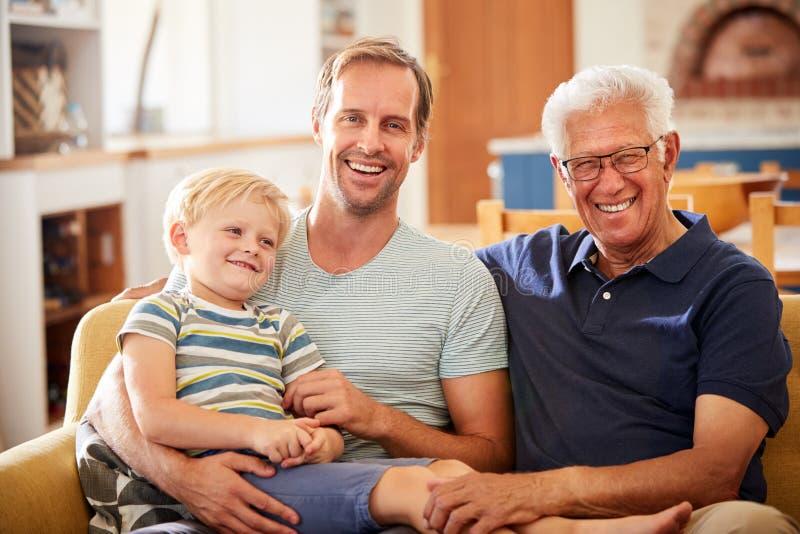 Portrait de père With Adult Son et de petit-fils détendant sur Sofa And Talking At Home photos stock