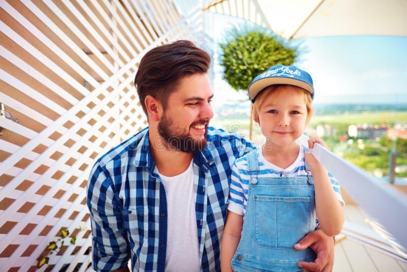 Portrait de père et de fils heureux, famille réparant la zone de patio de dessus de toit de la maison photo libre de droits