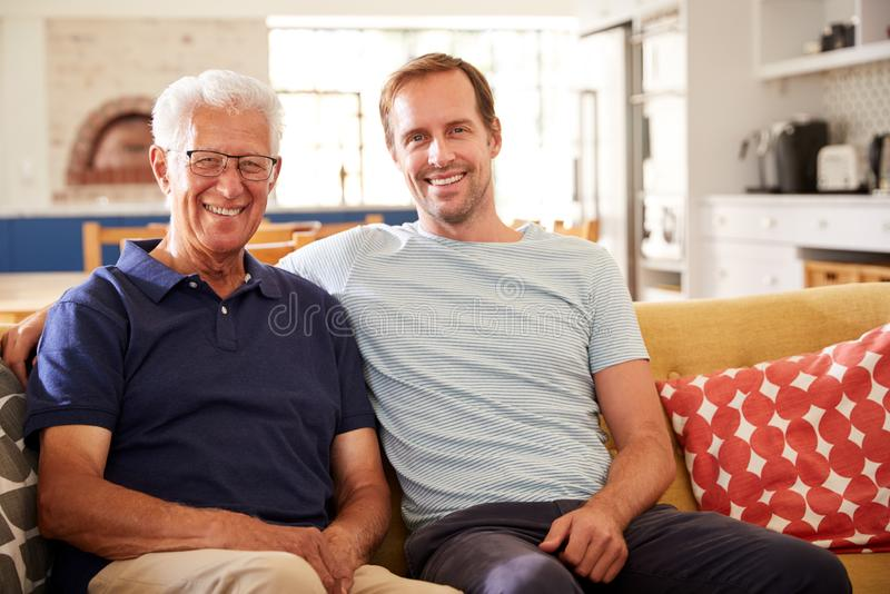 Portrait de père de sourire With Adult Son détendant sur Sofa At Home photo libre de droits
