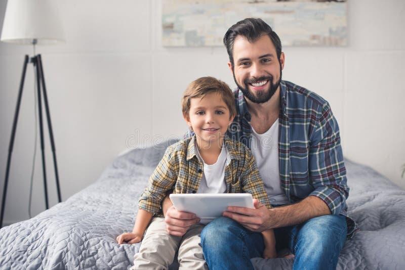 portrait de père de sourire avec le comprimé et le petit fils regardant l'appareil-photo images libres de droits