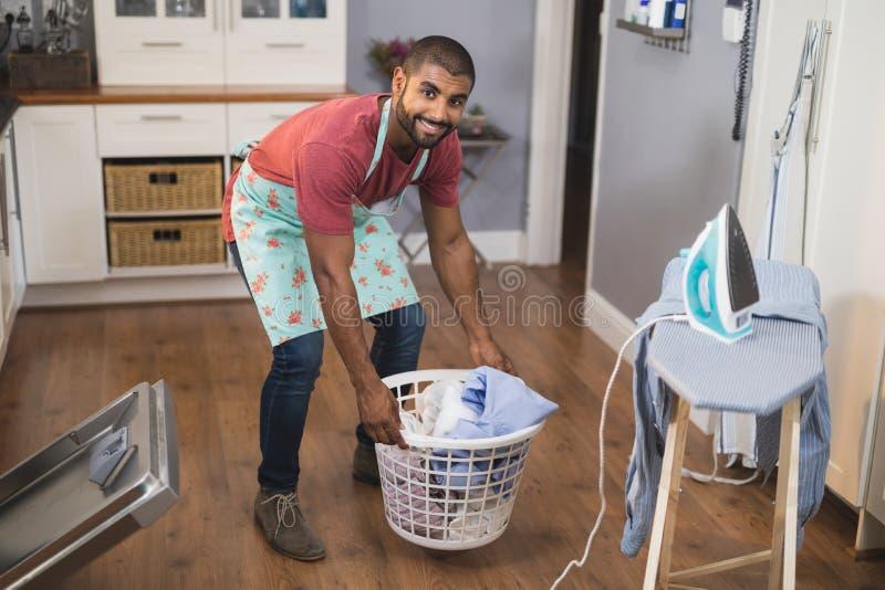 Portrait de panier de blanchisserie de levage de sourire d'homme par la planche à repasser dans la cuisine images stock