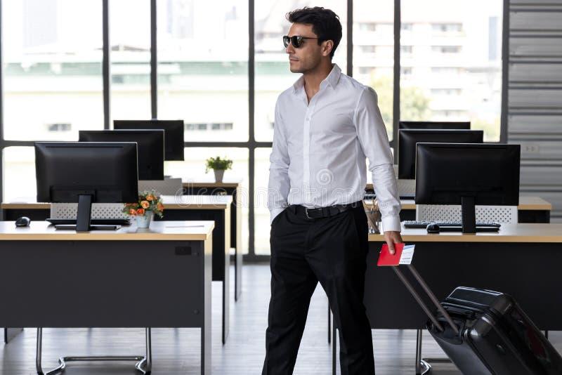 Portrait de passeport gai de participation d'homme d'affaires et bagage dans le lieu de travail du bureau Concept de vacances d'? photos stock