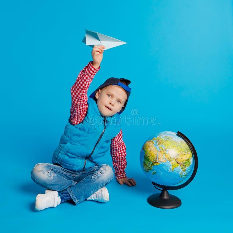 Portrait de petit garçon drôle avec l'avion de papier de chapeau et de jouet Représentation de l'endroit sur le globe, carte Voya images stock