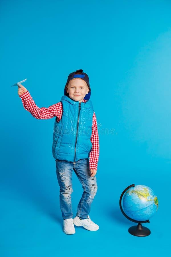Portrait de petit garçon drôle avec l'avion de papier de chapeau et de jouet Représentation de l'endroit sur le globe, carte Voya image libre de droits