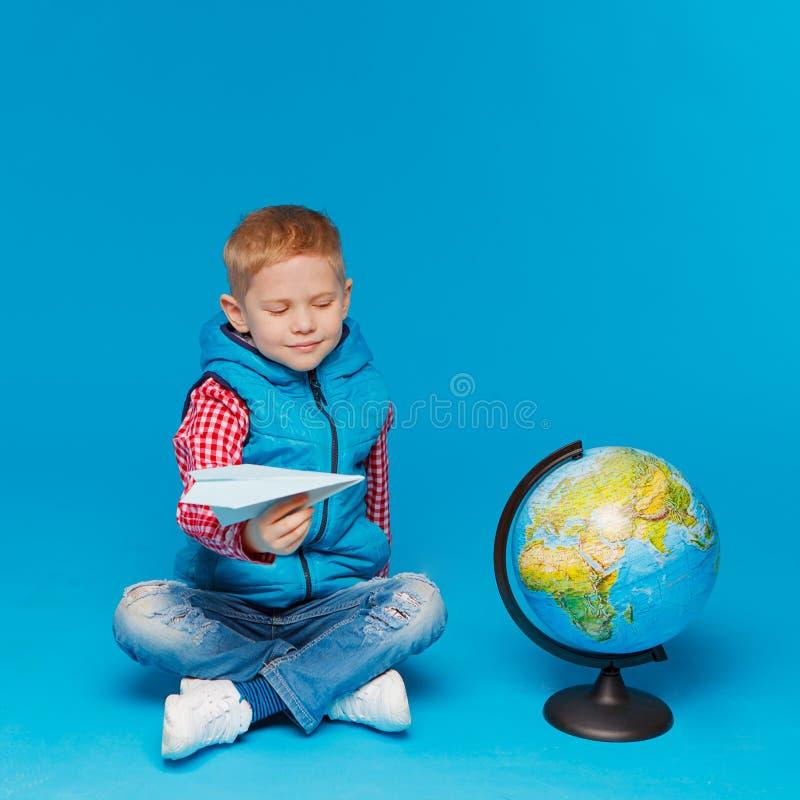 Portrait de petit garçon drôle avec l'avion de papier de jouet Représentation de l'endroit sur le globe, carte Voyage de concept, photographie stock libre de droits