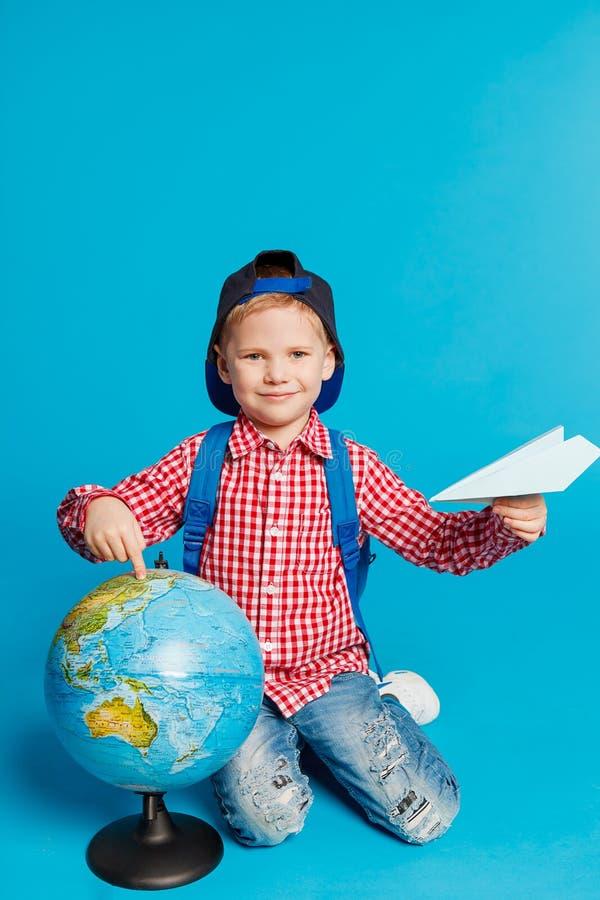 Portrait de petit garçon drôle avec l'avion de papier de sac à dos, de chapeau et de jouet Représentation de l'endroit sur le glo photos stock