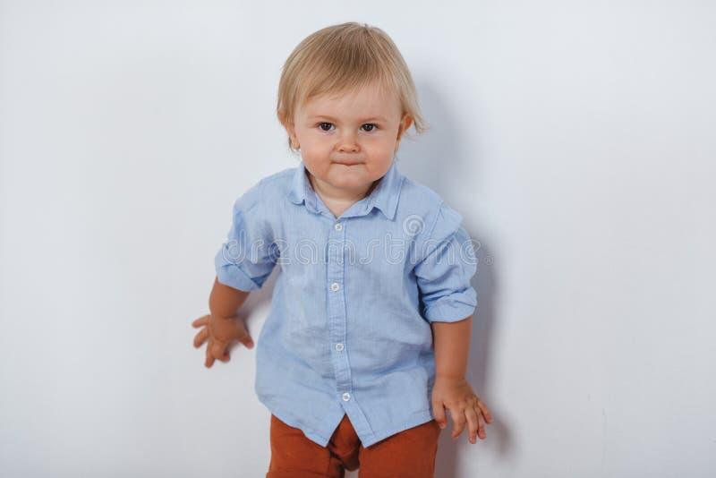 Portrait de petit garçon mignon de sourire près du mur blanc photo stock