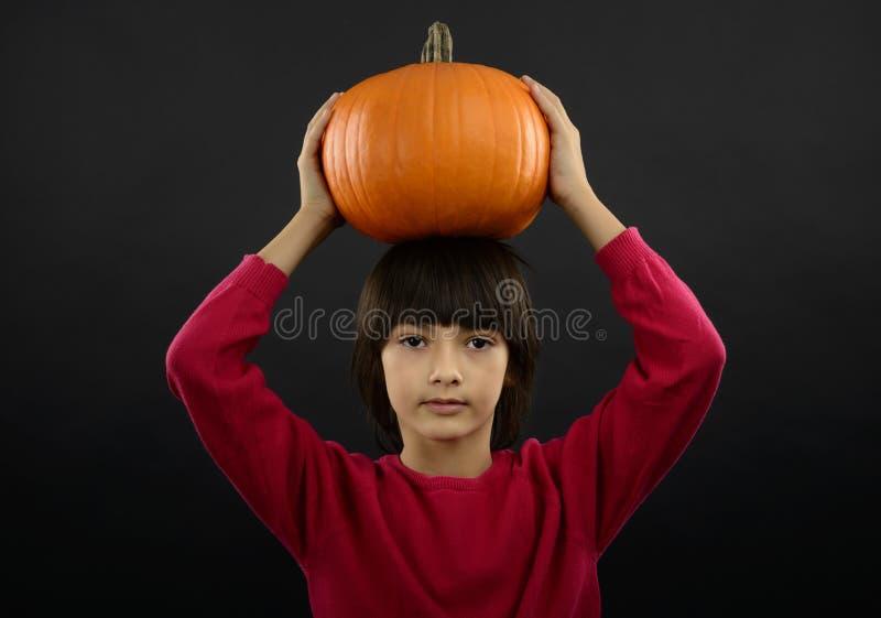 Portrait de petit garçon utilisant le costume de Halloween avec le potiron dessus photo libre de droits