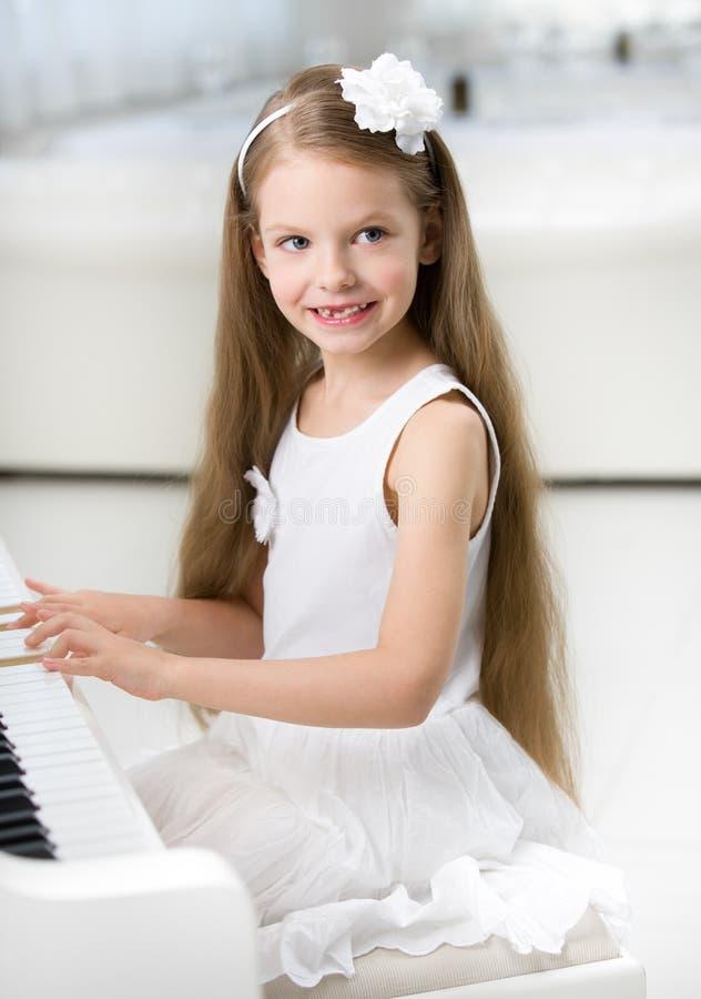 Portrait de petit pianiste dans la robe blanche jouant le piano photographie stock