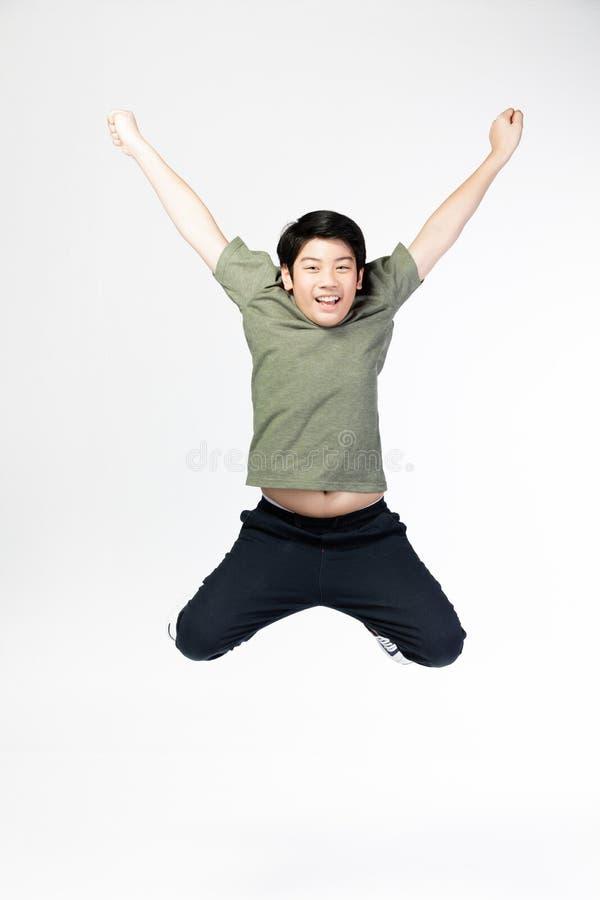 Portrait de petit sauter asiatique heureux d'enfant d'isolement sur le gris images libres de droits