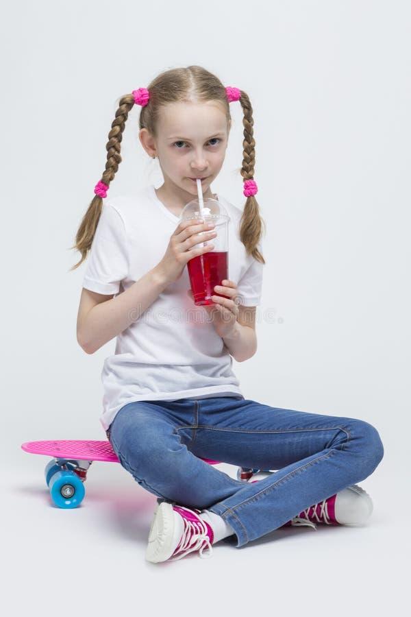 Portrait de petite fille blonde caucasienne avec de longs tresses posant avec Pennyboard rose photos libres de droits