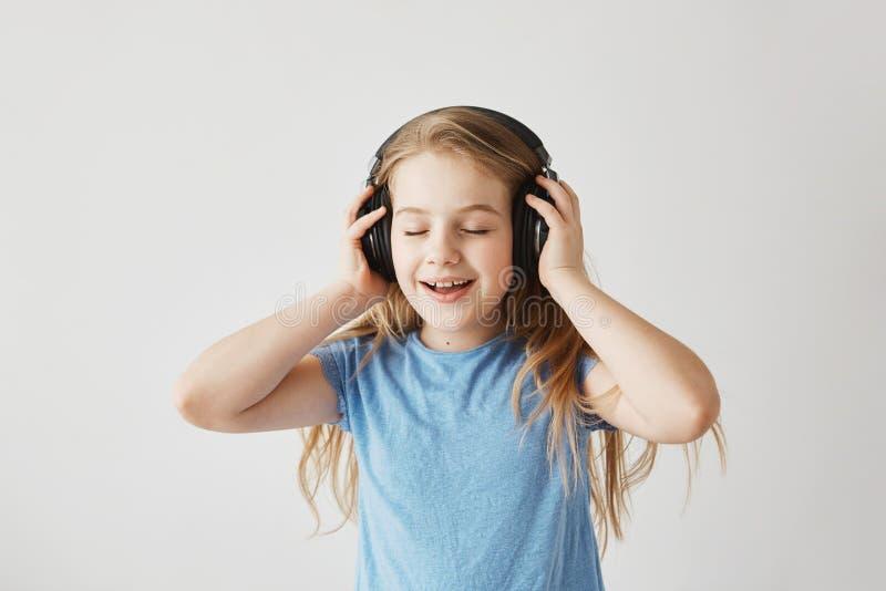 Portrait de petite fille blonde dans la chemise bleue jouant avec de grands écouteurs sans fil, écoutant la musique, chanson de c images libres de droits