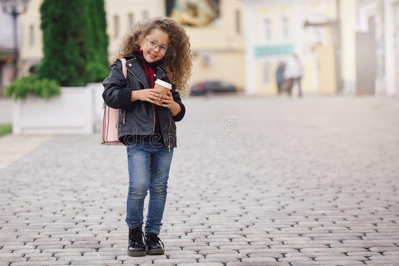 Portrait de petite fille bouclée de hippie en verres avec du café Type urbain Automne photos libres de droits