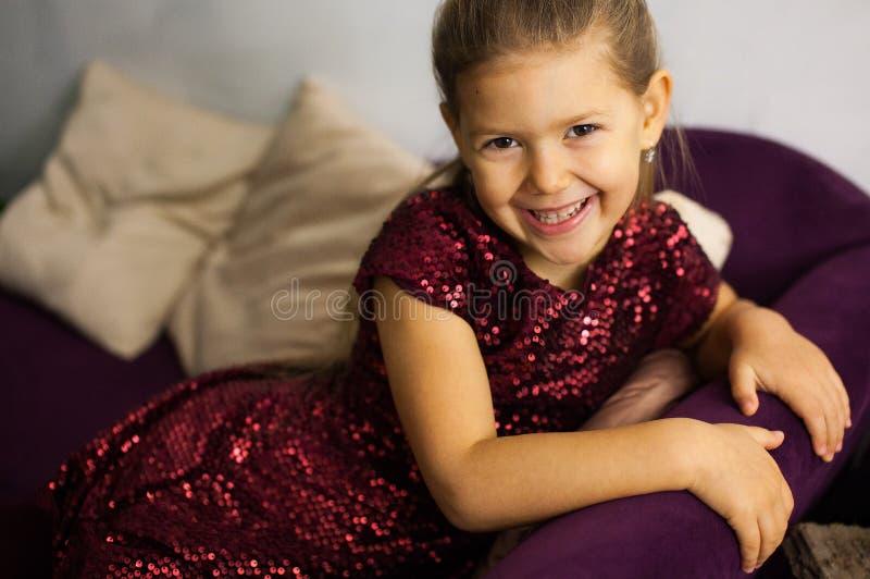 Portrait de petite fille dans la robe de bordo sur le sofa images libres de droits