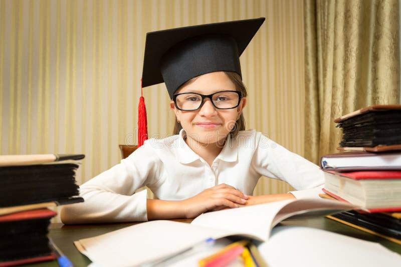 Portrait de petite fille de sourire dans le chapeau d'obtention du diplôme se reposant à l'étiquette photo stock