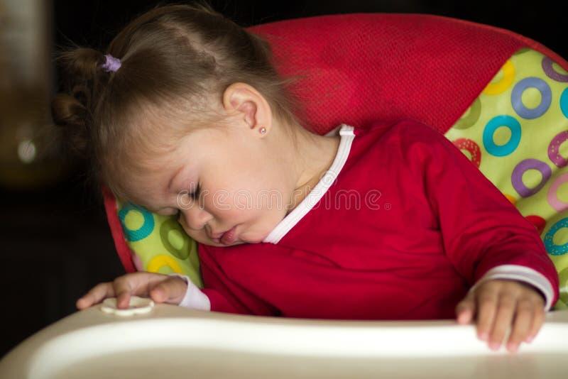 Portrait de petite fille dormant dans la chaise d'alimentation photo libre de droits