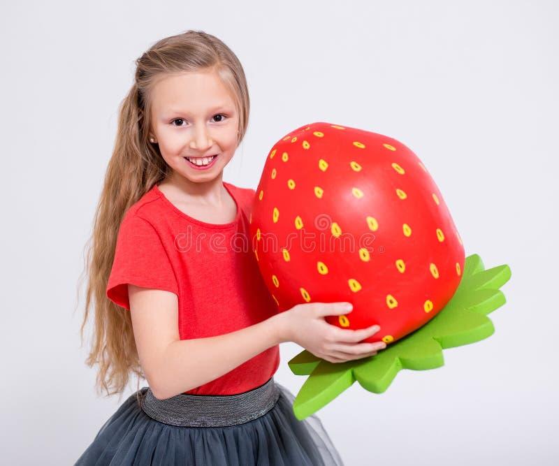 Portrait de petite fille mignonne avec la grande fraise artificielle au-dessus du blanc photos stock