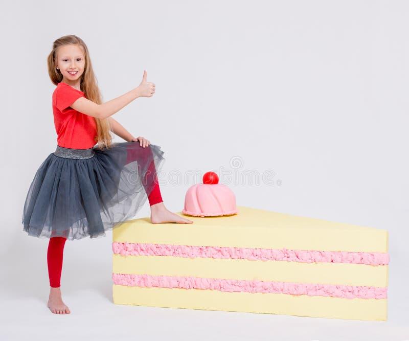 Portrait de petite fille mignonne avec la grande tranche de pouces de gâteau au-dessus de blanc photos libres de droits