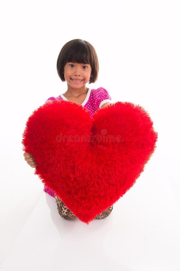 Portrait de petite fille tenant le coeur rouge au-dessus de l'Asiatique images stock