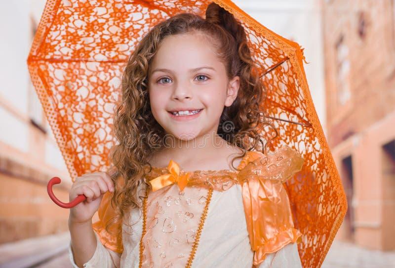 Portrait de petite fille utilisant un beau costume colonial et tenant un parapluie orange à un arrière-plan brouillé images libres de droits
