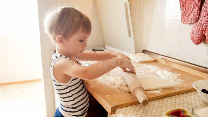 Portrait de peu de gar?on faisant la p?te sur le counterboard en bois de cuisine Tartes ou biscuits de cuisson d'enfant pour le n images libres de droits