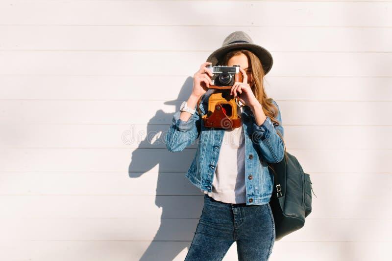Portrait de photographe féminin élégant dans le chapeau à la mode posant dehors avec la caméra professionnelle Fille de charme de images stock