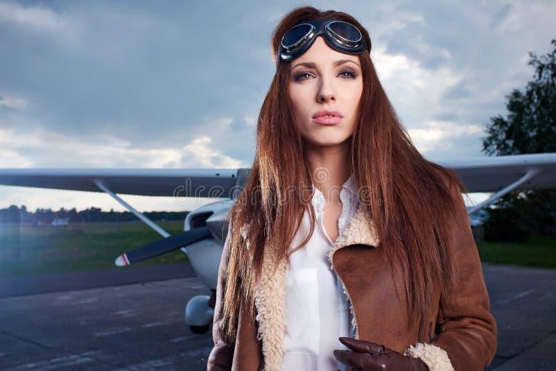 Portrait de pilote de jeune femme devant l'avion photos libres de droits
