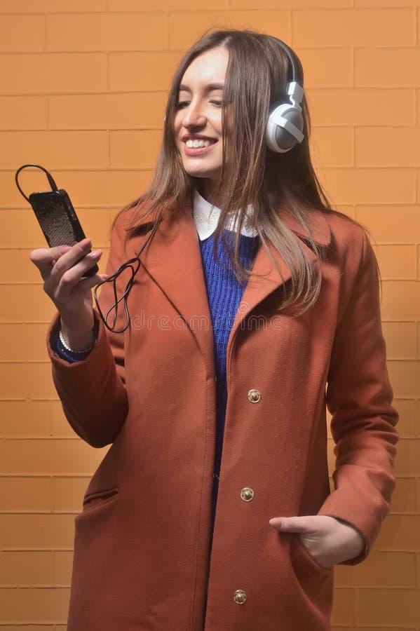 Portrait de plan rapproché de belle jeune femme appréciant la musique utilisant des écouteurs, d'isolement au-dessus de l'orange image libre de droits