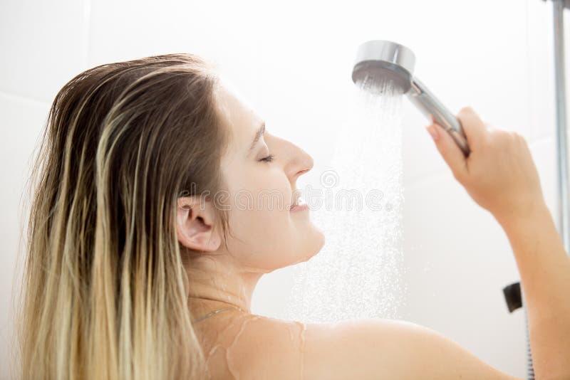 Portrait de plan rapproché de belle jeune femme se tenant sous la douche image libre de droits
