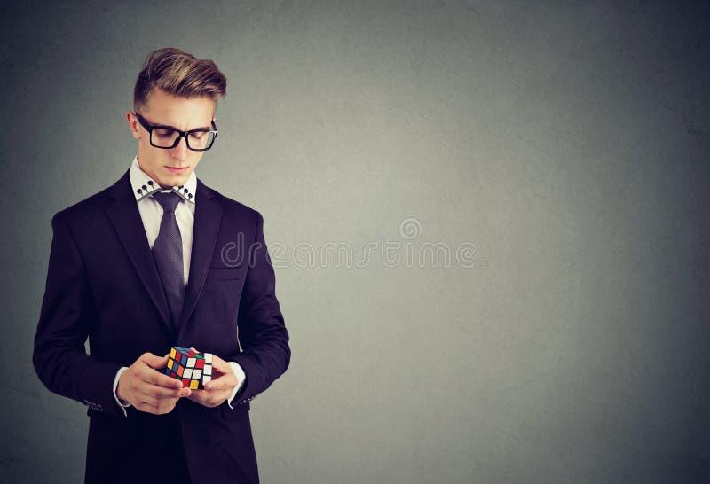 Portrait de plan rapproché d'homme sérieux dans des lunettes tenant le cube en rubik photographie stock libre de droits
