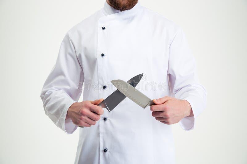 Portrait de plan rapproché d'un cuisinier masculin de chef affilant le couteau photos libres de droits