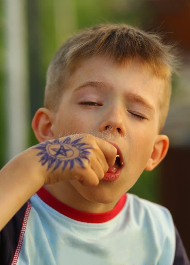 Portrait de plan rapproché d'un garçon mangeant des chips avec des yeux fermés photo stock
