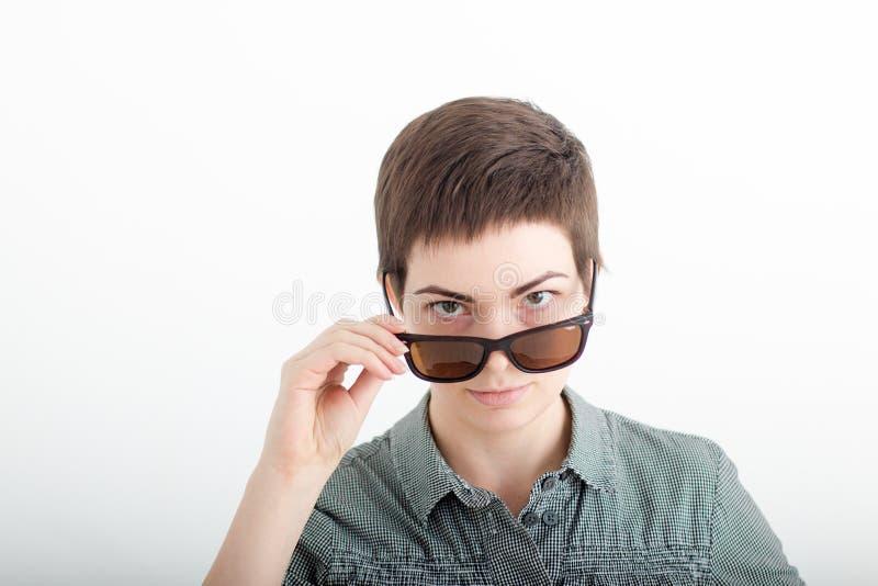 Portrait de plan rapproché d'une belle jeune femme sur le fond blanc avec les cheveux courts foncés regardant au-dessus des lunet photo stock