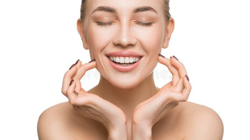 Portrait de plan rapproché d'une femme de sourire avec les dents saines blanches, et toucher le visage d'isolement sur le fond bl photos stock