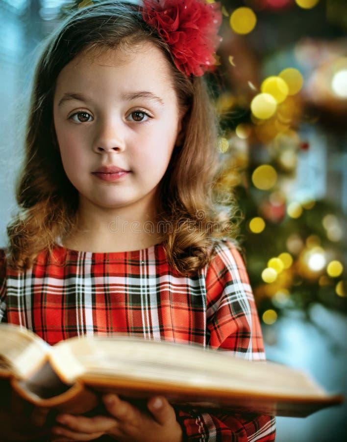 Portrait de plan rapproché d'une fille mignonne et petite tenant un livre photographie stock libre de droits