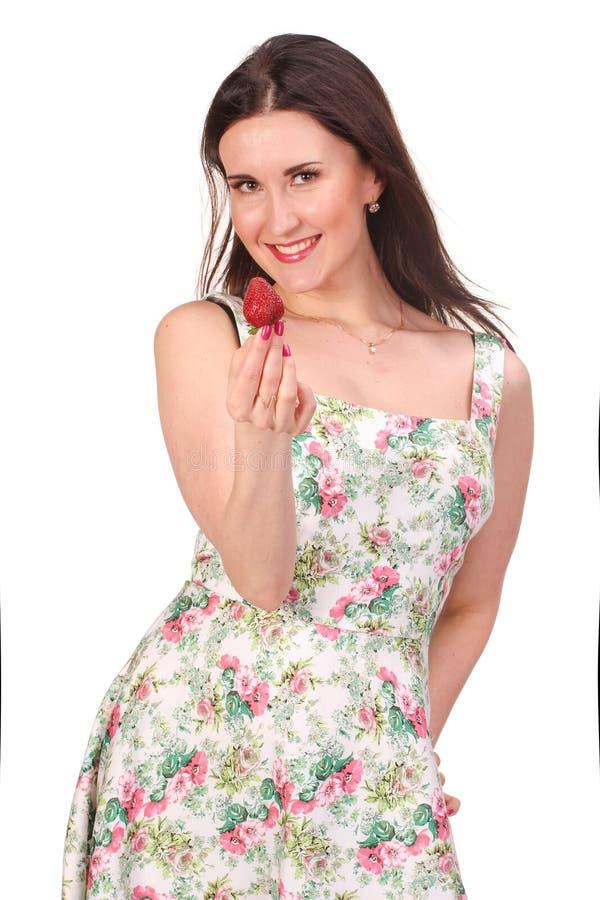 Portrait de plan rapproché d'une jeune femme mangeant la fraise photographie stock
