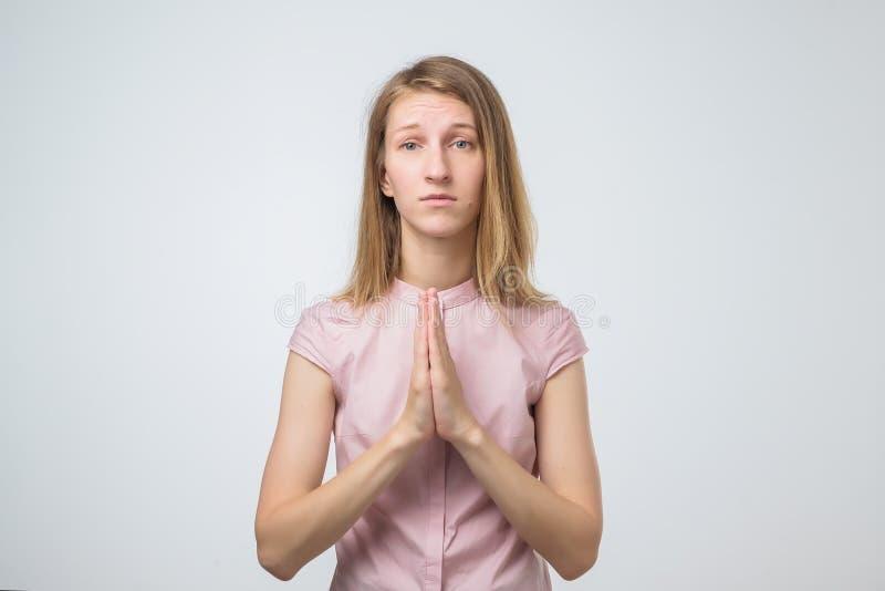 Portrait de plan rapproché d'une jeune femme triste priant, espérant, priant pour le meilleur d'isolement sur le fond blanc photos stock
