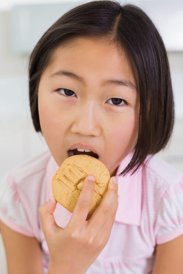 Portrait de plan rapproché d'une jeune fille mangeant le biscuit photo libre de droits