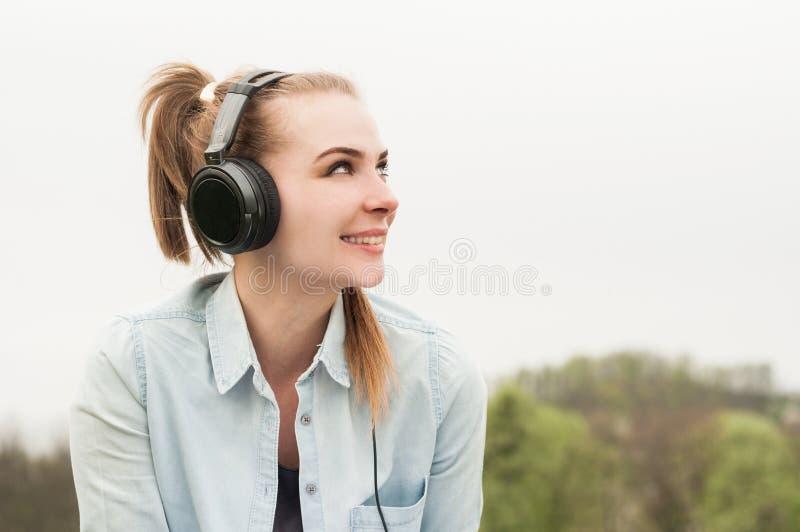 Portrait de plan rapproché de belle femme de sourire avec des écouteurs image stock