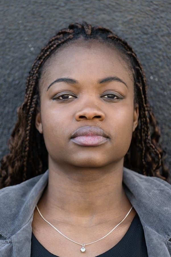 Portrait de plan rapproché de belle jeune femme africaine sur le backgr gris photos stock