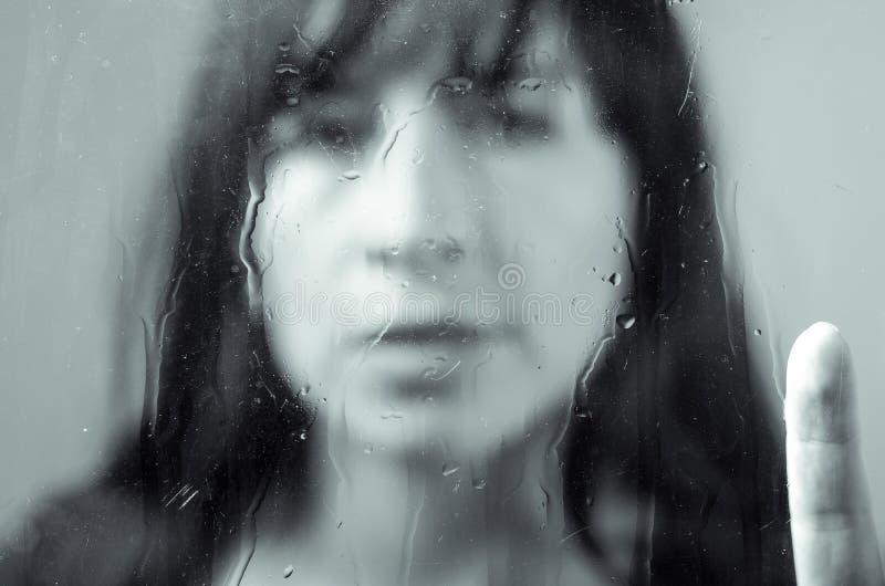 Portrait de plan rapproché de fille de brune derrière le verre photographie stock