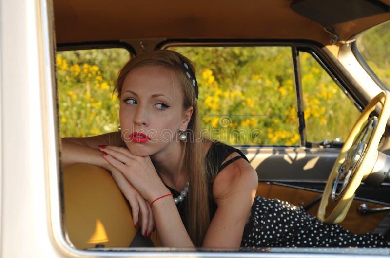 Portrait de plan rapproché de jeune femme à l'intérieur de voiture démodée image libre de droits