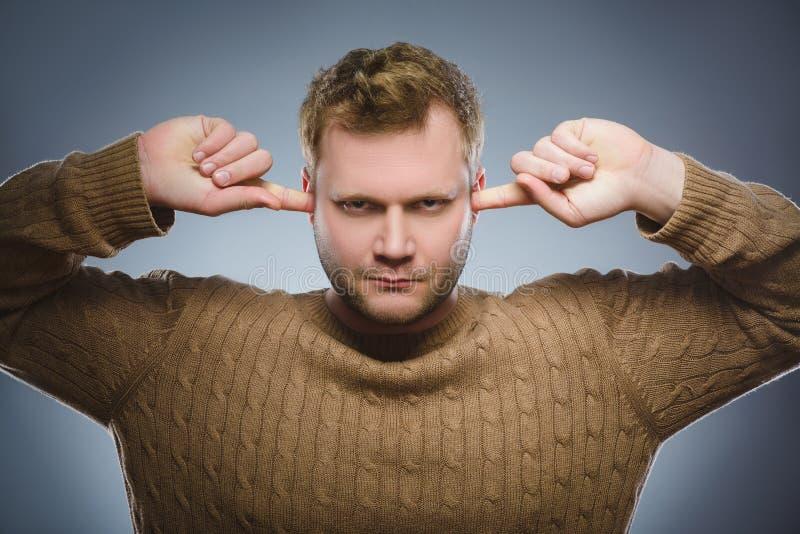 Portrait de plan rapproché de l'homme inquiété couvrant ses oreilles, observant N'entendez rien images stock