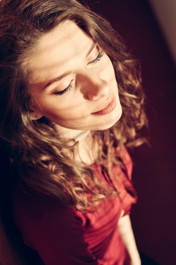 Portrait de plan rapproché de la belle jeune femme bouclée de mode se dorant dans les yeux de détente de lumière du soleil fermés photo libre de droits