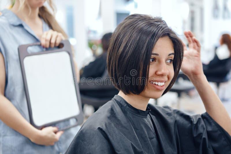 Portrait de plan rapproché de la femme latine hispanique de fille s'asseyant dans la chaise dans le salon de coiffure images libres de droits